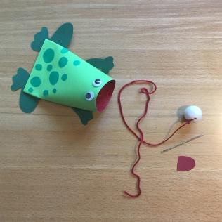 Befestige die Kugel an der Schnur und klebe das andere Ende mit einem Stück roter Pappe ins Froschmaul!
